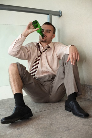 Businessman sitting on the floor drinking beer photo