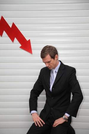 kneeling man: Businessman with arrow pointing down on him