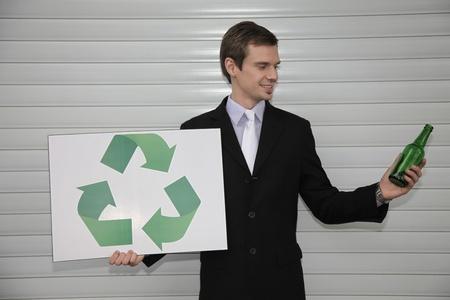 Businessman holding a card with recycling symbol and a glass bottle Stock Photo - 13355101