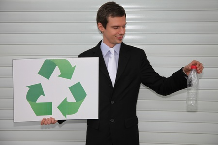 Businessman holding a card with recycling symbol and a plastic bottle Stock Photo - 13354130