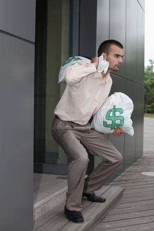 corporate greed: Businessman walking out from building holding money bags Stock Photo
