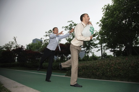 Businessman carrying money bag being chased by a colleague photo