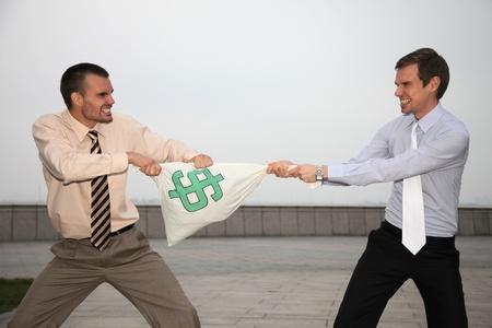 gritting: Businessmen pulling at money bag