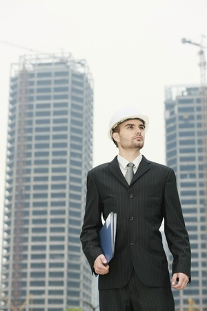 scandinavian descent: Businessman with hard hat holding a file at a construction site