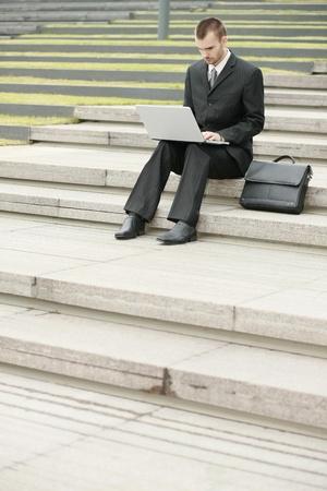 scandinavian descent: Businessman using laptop outdoors