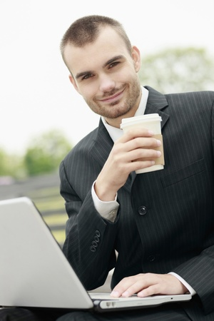 Businessman drinking coffee while using laptop photo