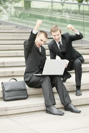 Businessmen looking at laptop and raising fist Stock Photo - 13355277