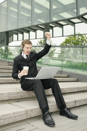 cheer full: Businessman using laptop with fist raised Stock Photo