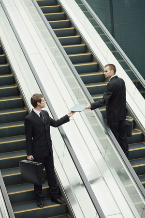 Businessman passing a file to his colleague Stock Photo - 13355243