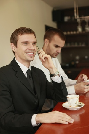 scandinavian descent: Businessman talking on the phone while his colleague is text messaging on the phone