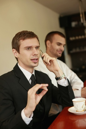 scandinavian descent: Businessman talking on the phone while his colleague smiling in the background