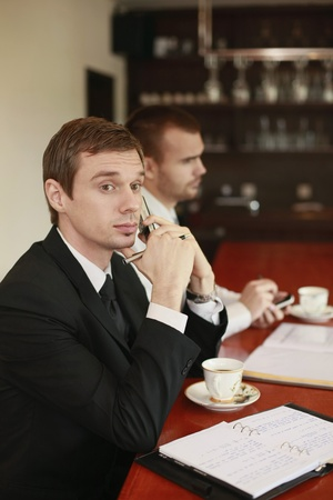 Businessman talking on the phone while his colleague is text messaging on the phone Stock Photo - 13355768
