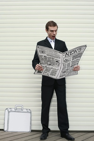 Businessman looking shocked while reading newspaper Stock Photo - 13357006