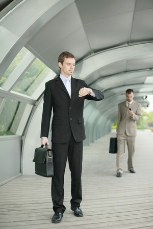 business briefcase: Businessman looking at his watch while another businessman is in the background