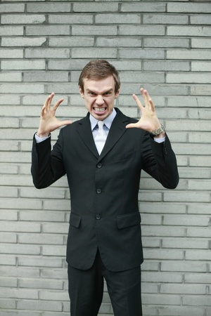clenching teeth: Businessman clenching teeth and making hand gestures