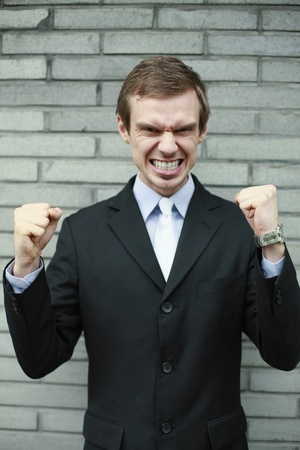 clenching teeth: Businessman clenching teeth and showing fists
