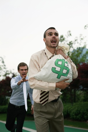 scandinavian descent: Businessman carrying money bag being chased by a colleague