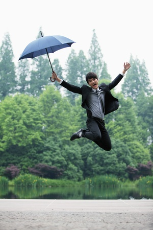 Businessman with an umbrella jumping in the air photo