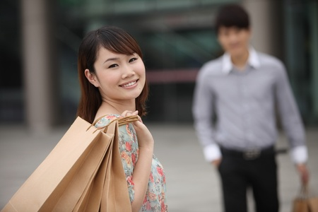Woman with shopping bags, man in the background photo
