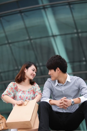 Man and woman sitting on stairs after shopping photo