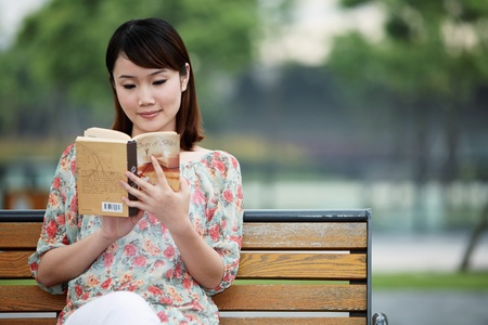 Woman sitting on bench reading book Stock Photo - 13355203