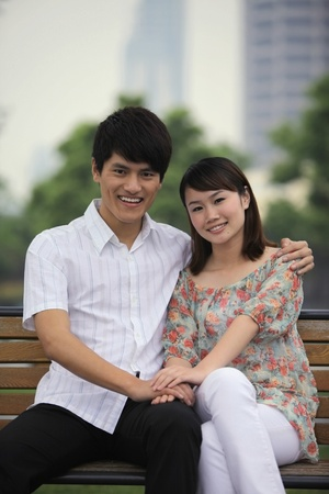 Man and woman sitting on a bench, smiling Stock Photo - 13355114