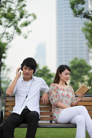 Man listening to music on the headphones, woman reading book on the bench Stock Photo - 13354888