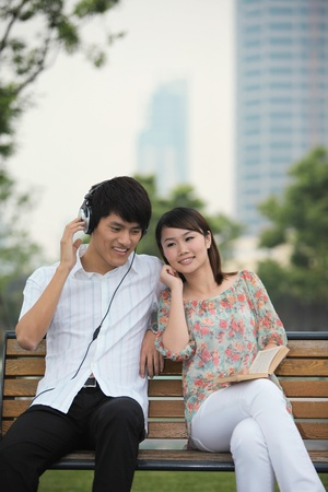 Man listening to music on the headphones, woman reading book on the bench Stock Photo - 13355102