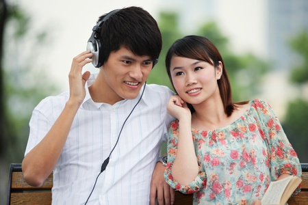 Man listening to music on the headphones, woman reading book on the bench Stock Photo - 13355051