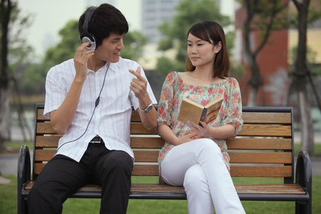 man holding book: Man listening to music on the headphones, woman reading book on the bench Stock Photo