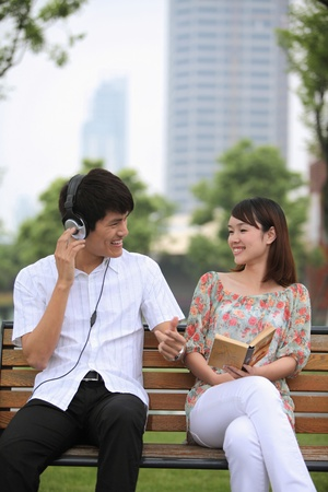 Man listening to music on the headphones, woman reading book on the bench Stock Photo - 13355140