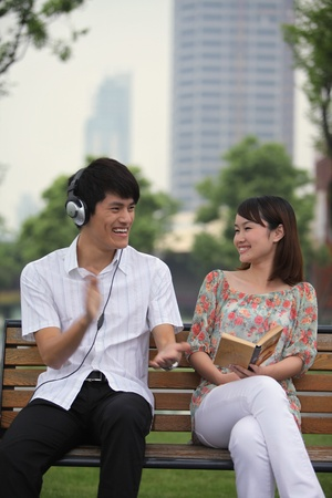 Man listening to music on the headphones, woman reading book on the bench Stock Photo - 13355099
