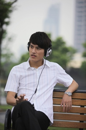 Man sitting on bench listening to music on the headphones photo
