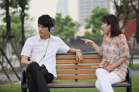 Man listening to music on the headphones, woman scolding man Stock Photo - 13355181