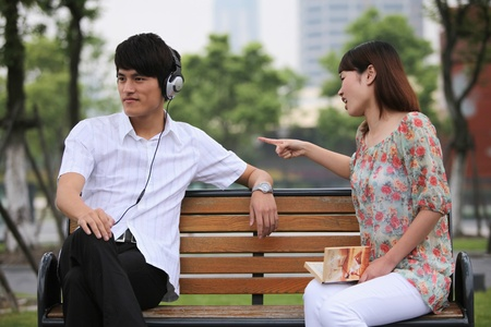 Man listening to music on the headphones, woman scolding man photo