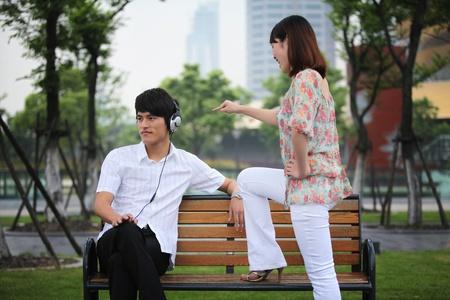 Man listening to music on the headphones, woman scolding man Stock Photo - 13355161