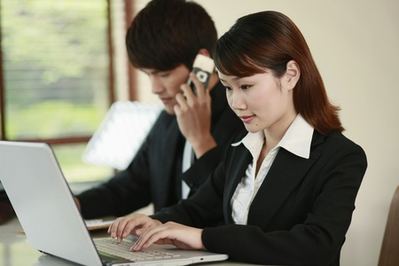 Businesswoman using laptop, businessman talking on the phone in the background photo