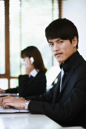 Businessman using laptop, businesswoman talking on the phone in the background photo