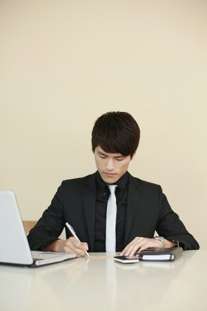 Businessman signing cheque with pen photo