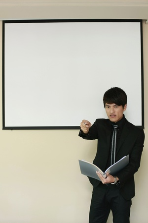 Businessman pointing at the audience while giving presentation Stock Photo - 13355384