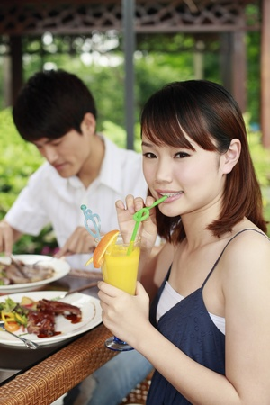 Woman with a glass of orange juice, man eating in the background photo