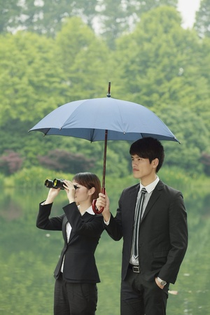 Businesswoman looking through binoculars, businessman shielding her with an umbrella Stock Photo - 13361289