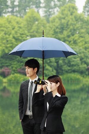 Businesswoman looking through binoculars, businessman shielding her with an umbrella Stock Photo - 13361451