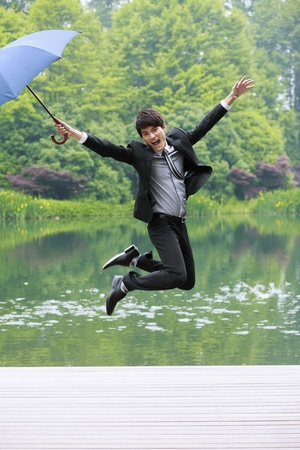 Businessman with an umbrella jumping in the air Stock Photo - 13361425