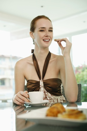 Woman enjoying breakfast of pastry and coffee at bakery photo