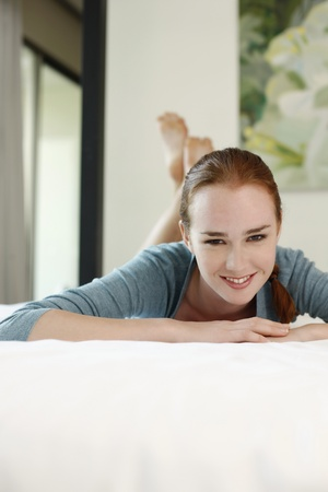 Woman lying on bed smiling photo