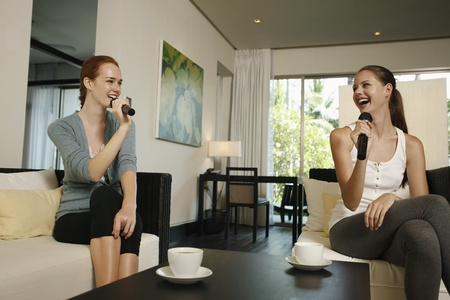 Women singing karaoke together photo