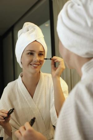 Woman applying mascara photo
