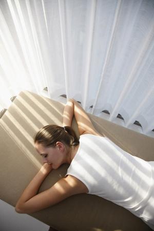 Woman lying down on lounge chair photo