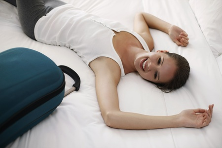 Woman lying down on bed with luggage at the side photo